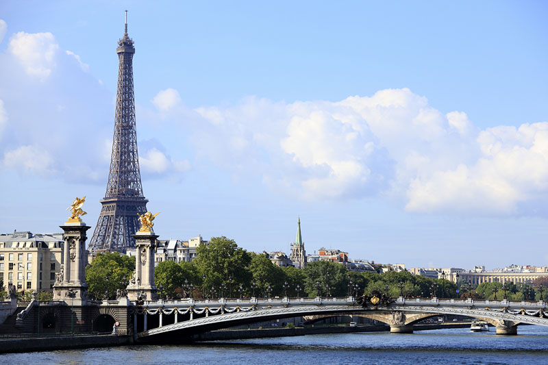 Paris scene with River Seine, Pont Alexandre III and skyline with Eiffel Tower in the distance.